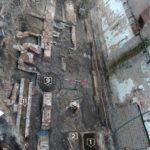 Foto van de plek waar het archeologisch onderzoek plaatsvond.. De rechtergevel is die van het Veilinghuisje aan de bovenzijde ligt de Warmoesstraat. 1 Is een waterkelder, 2 en 11 zijn bakstenen goten waarvan de laatste waarschijnlijk loosde op de Oudezijds Voorburgwal, 6 is een waterput, 18 een intacte overwelfde waterkelder en in de put 9 is een fragment van en suikerstrooppot gevonden.