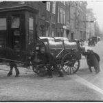De winkelpui met daarvoor de vuilnisophaaldienst in 1937.