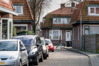 Man in straat vol geparkeerde auto's in woonwijk.