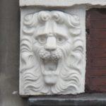 Linker leeuwenmasker in de gevel.