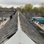 Restauratie in volle gang. Zicht op de voormalige wagenschuur (rechtsachter) vanaf het dak gezien