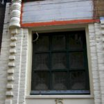 Detail van de pui zonder reclame, voor restauratie.