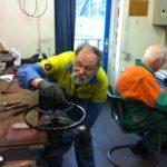 Vrijwilligers knappen het gangrad van het torenuurwerk op