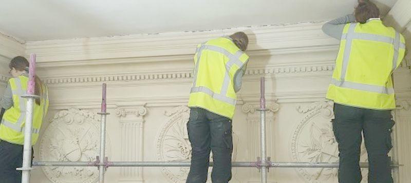 Stagiaires restaureren trappenhuis van de manege
