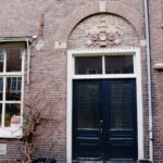 De dubbele gevelsteen is meeverhuisd met het St. Jacobsgodshuis en later teruggeplaatst in de achtergevel van Hagestraat 10, aan de binnenplaats